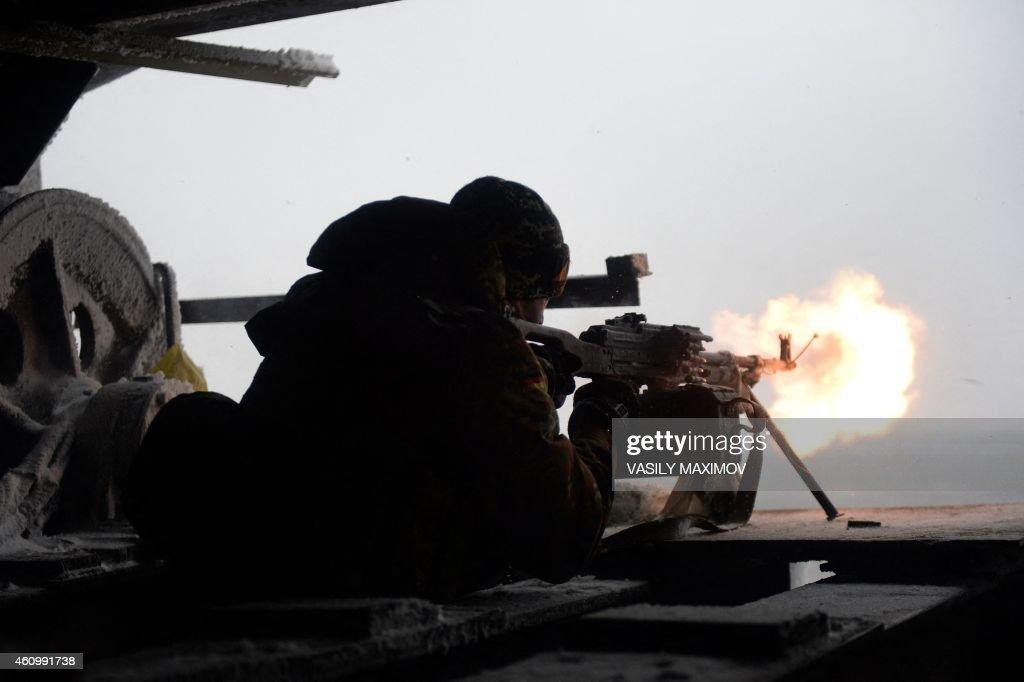 An Ukrainian Right Sector batallion volunteer fires a machine gun on January 3 2015 from his position near the eastern Ukrainian village of Pisky in...