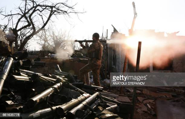 TOPSHOT An Ukrainian serviceman shots with a grenade launcher during fighting with proRussian separatists in Avdiivka Donetsk region on March 30 2017...