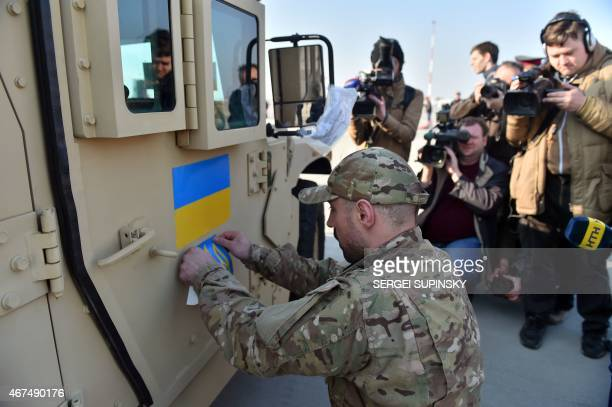 An Ukrainian serviceman sticks an Ukrainian flag and the state emblem on an Humvee at Kiev airport on March 25 2015 during a welcoming ceremony of...
