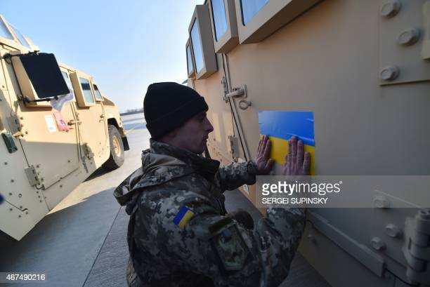 An Ukrainian serviceman sticks an Ukrainian flag on a Humvee at Kiev airport on March 25 2015 during a welcoming ceremony of the first US plane...