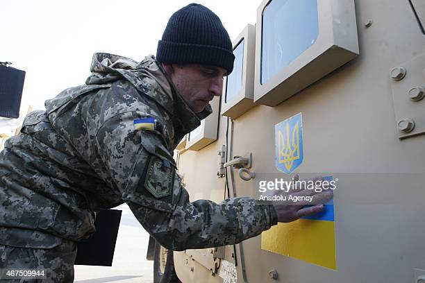 An Ukrainian serviceman sticks an Ukrainian flag on an armored vehicle at Boryspil airport in Kiev on March 25 2015 during a welcoming ceremony of...