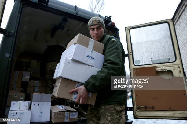 An Ukrainian serviceman unloads warm clothes distributed as humanitarian aid to local residents in Avdiivka Donetsk region on February 5 2017...
