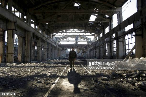 TOPSHOT An Ukrainian serviceman walks through the rubble of a destroyed workshop after fighting with proRussian separatists in Avdiivka Donetsk...