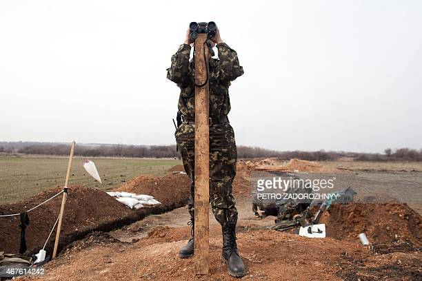An Ukrainian soldier looks through binoculars on the position of Ukrainian forces not far from Lysychansk Lugansk region on March 26 2015 The United...
