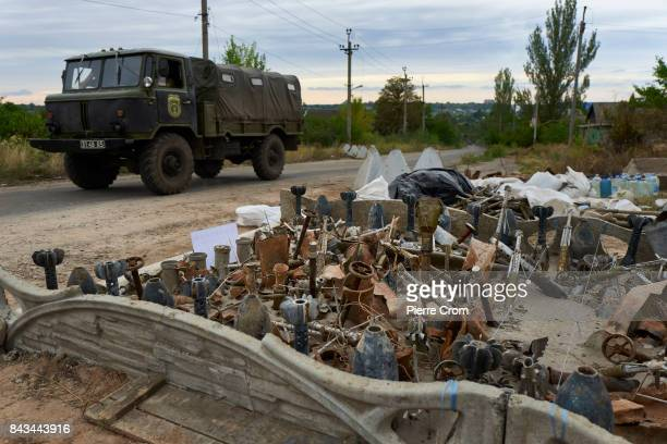 An Ukrainian vehicle drives by a new monument build with remains of artillery projectiles on September 06 2017 in Avdiivka Ukraine The frontlinecity...