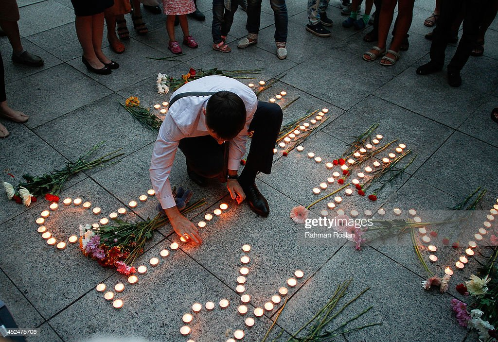 An Ukranian man lights up candles during a candle light vigil for the victims of MH17 on July 21, 2014 in Kuala Lumpur, Malaysia. Malaysian Airlines flight MH17 was travelling from Amsterdam to Kuala Lumpur when it crashed killing all 298 on board including 80 children. The aircraft was allegedly shot down by a missile and investigations continue over the perpetrators of the attack.