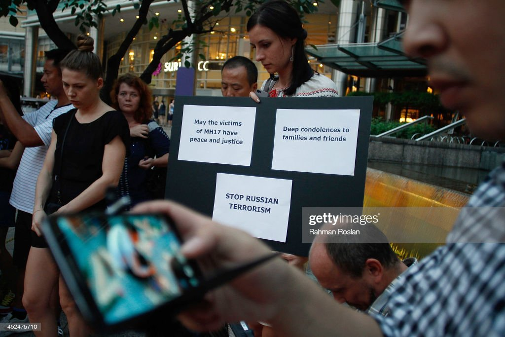 An Ukranian woman holds a placard condeming Russia during a candle light vigil for the victims of MH17 on July 21, 2014 in Kuala Lumpur, Malaysia. Malaysian Airlines flight MH17 was travelling from Amsterdam to Kuala Lumpur when it crashed killing all 298 on board including 80 children. The aircraft was allegedly shot down by a missile and investigations continue over the perpetrators of the attack.