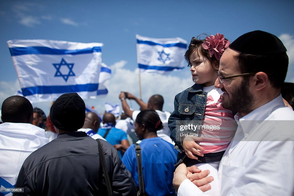 An Ultra orthodox Israeli man holds his baby as people celebrate the 65th anniversary of Israel's independence on April 16, 2013 in Tel Aviv, Israel. The day marks when David Ben-Gurion, the Executive Head of the World Zionist Organization declared the establishment of a Jewish state in Eretz- Israel.