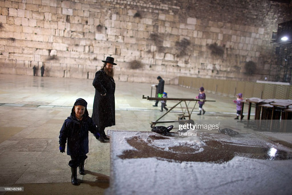 An Ultra orthodox Jewish boy plays as snow falls at the western wall on January 9, 2013 in Jerusalem's old city, Israel. Snow and strong winds have affected regions across the Middle East.