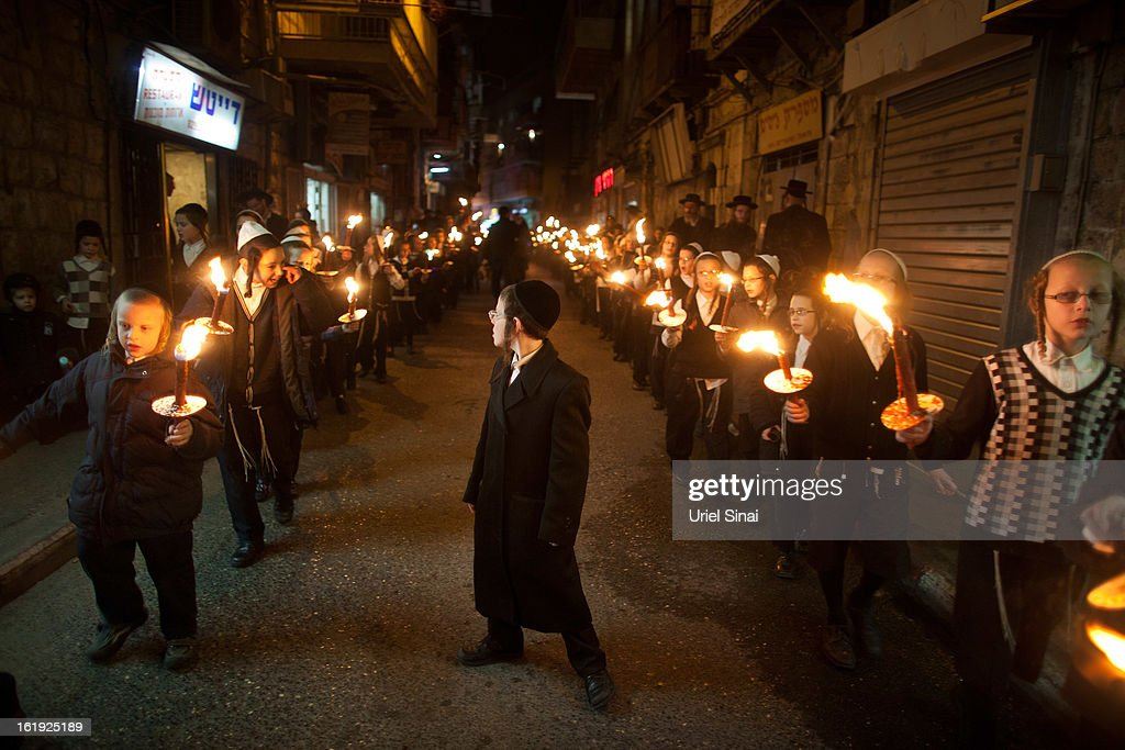 An Ultra Orthodox Jewish children of the Ultra-Orthodox Tholdot Avraham Yizhak Hasidic dynasty march with torches during an inauguration ceremony for the holy book in an Ultra Orthodox neighborhood of Mea Shearim on February 17, 2013 in Jerusalem, Israel. The Torah is also known as the first five books of Moses. Hundreds of Ultra Orthodox Jews marched and danced with the Torah through the neighbourhood into the synagogue where they place the Torah.