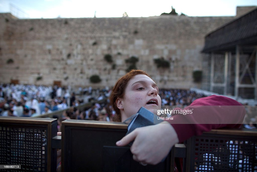 An Ultra Orthodox Jewish girl looks over a barrier as members of the religious group 'Women Of The Wall' hold a prayer service to mark the first day of the Jewish month of Sivan at the Western Wall on May 10, 2013 in Jerusalem, Israel. Thousands of ultra-Orthodox protestors clashed with Israeli police during the first monthly prayer service to be held by Women Of The Wall following the recent landmark ruling by Jerusalem District Court allowing women to wear prayer shawls at the Western Wall.