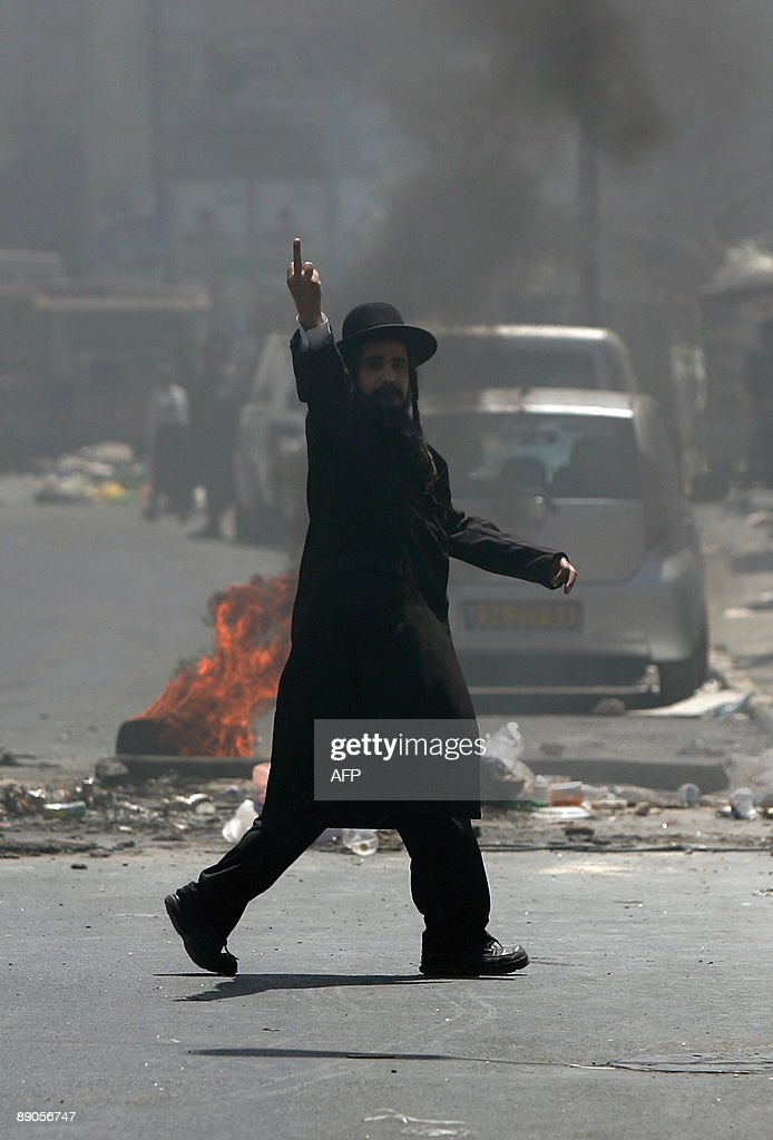 An Ultra Orthodox Jewish man gestures during clashes with Israeli forces following demonstrations against the arrest of a woman accused of child abuse in Jerusalem on July 16, 2009. Hundreds of ultra-Orthodox Jews clashed with police for a third day in protest at an 'unjustified' arrest of a religious woman and the opening of a parking lot on Saturdays, the Jewish holy day of rest.