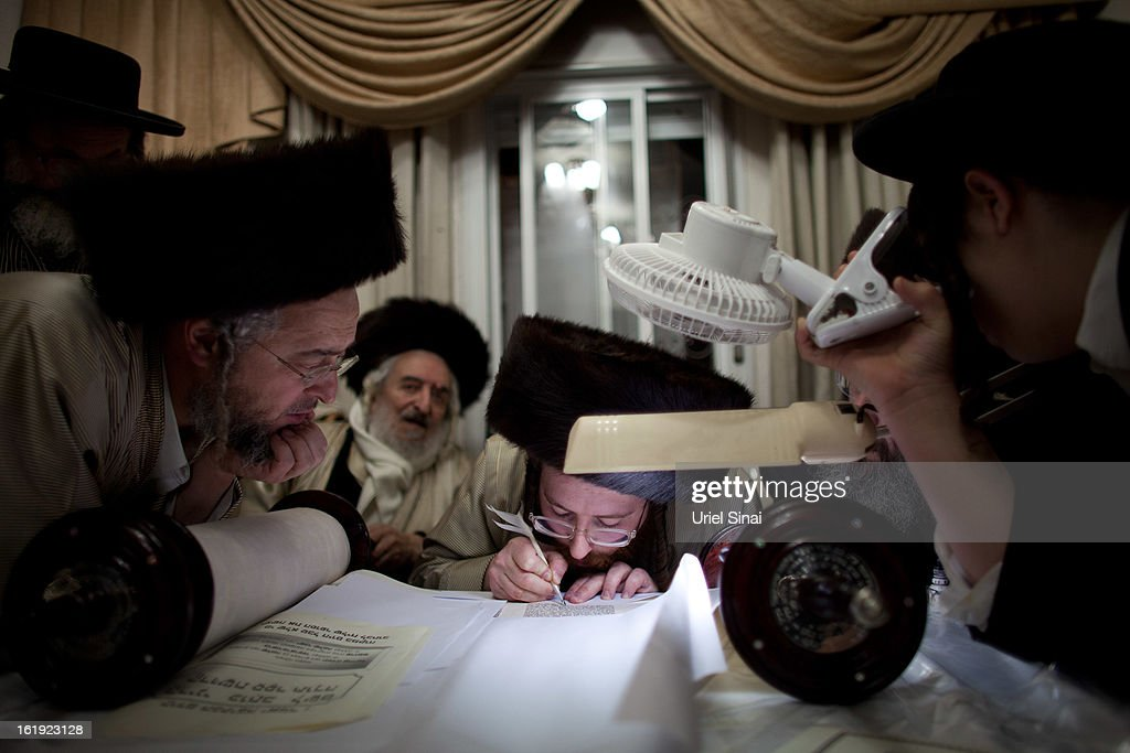 An Ultra Orthodox Jewish man of the Ultra-Orthodox Tholdot Avraham Yizhak Hasidic dynasty uses a quill to write the last letters of a Torah scroll during an inauguration ceremony for the holy book in an Ultra Orthodox neighborhood of Mea Shearim on February 17, 2013 in Jerusalem, Israel. The Torah is also known as the first five books of Moses. Hundreds of Ultra Orthodox Jews marched and danced with the Torah through the neighbourhood into the synagogue where they place the Torah.