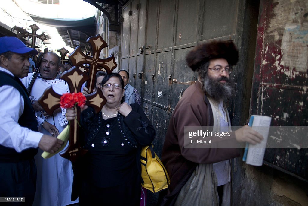 An Ultra Orthodox Jewish man passes next to Orthodox Christian pilgrims holding wooden crosses as they take part in the Good Friday procession along the Via Dolorosa on April 18, 2014 in Jerusalem's old city, Israel.Thousands of Christian pilgrims from around the world have flocked to the Holy City to mark Good Friday and pray along the traditional route Jesus Christ took to his crucifixion, leading up to his resurrection on Easter.