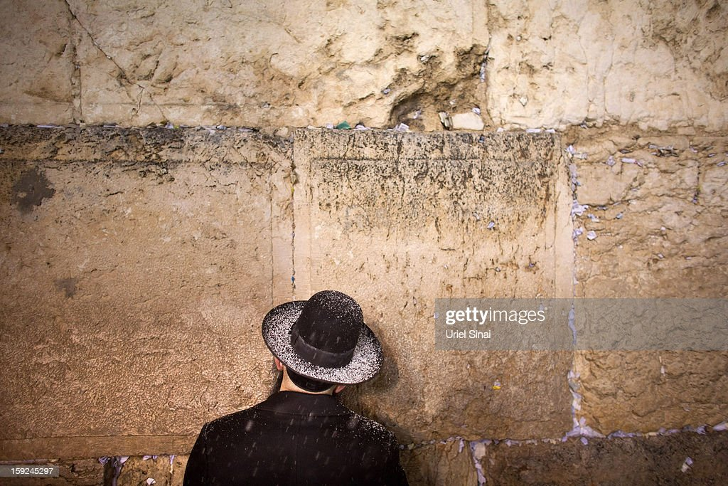 An Ultra orthodox Jewish man prays as snow falls at the western wall on January 9, 2013 in Jerusalem's old city, Israel. Snow and strong winds have affected regions across the Middle East.