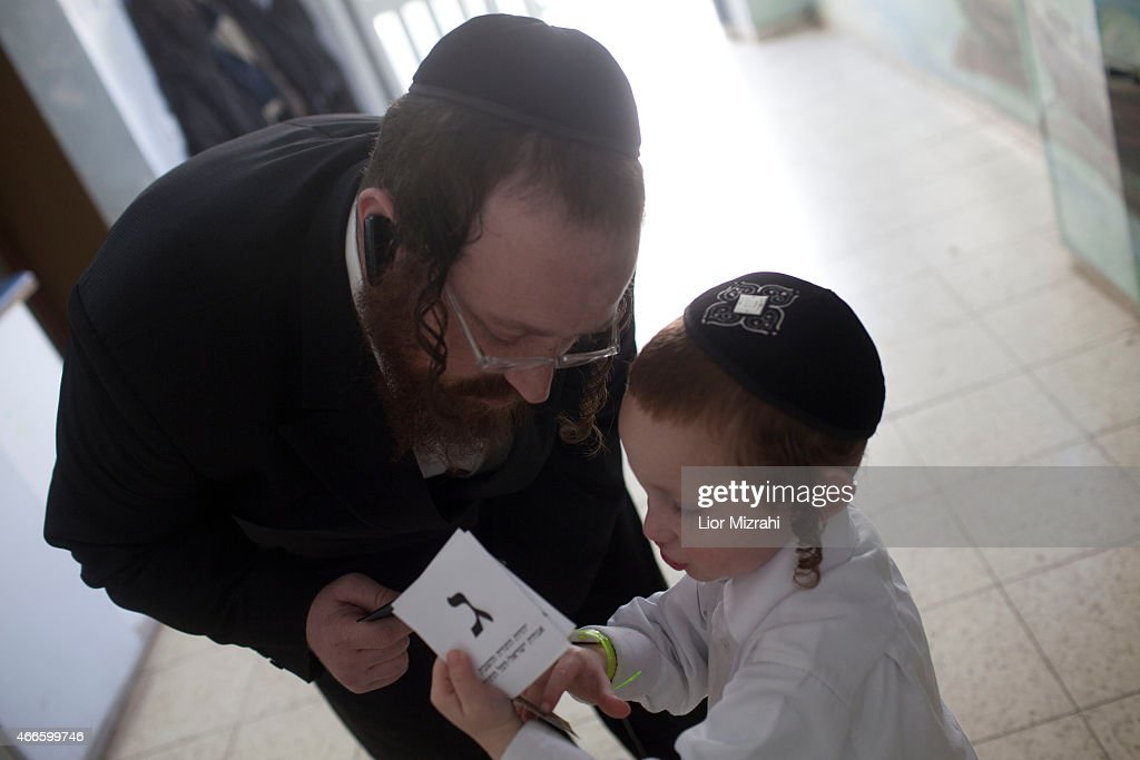 An Ultra Orthodox Jewish man stands with his son outside a polling station on election day on March 17 2015 in Kiryat Ye'arim Israel Israel's general...