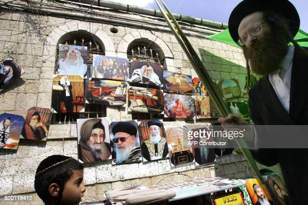 An Ultra Orthodox Jewish man walks next to images of Rabbis which are for sale as he carries Lulav one of four species to be used during the...