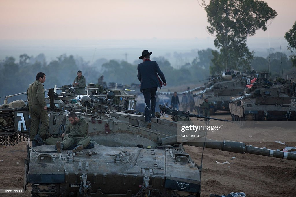 An Ultra orthodox Jewish man walks on top of a tank as Israeli soldiers prepare weapons and vehicles in a deployment area on November 22, 2012 on Israel's border with the Gaza Strip. The ceasefire between Israel and Hamas appears to be holding despite rockets being fired from Gaza. During the night the IDF reportedly arrested a number of 'terror operatives' in the West Bank in continued efforts to restore peace in the region.