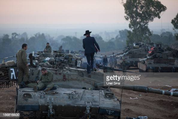 An Ultra orthodox Jewish man walks on top of a tank as Israeli soldiers prepare weapons and vehicles in a deployment area on November 22 2012 on...