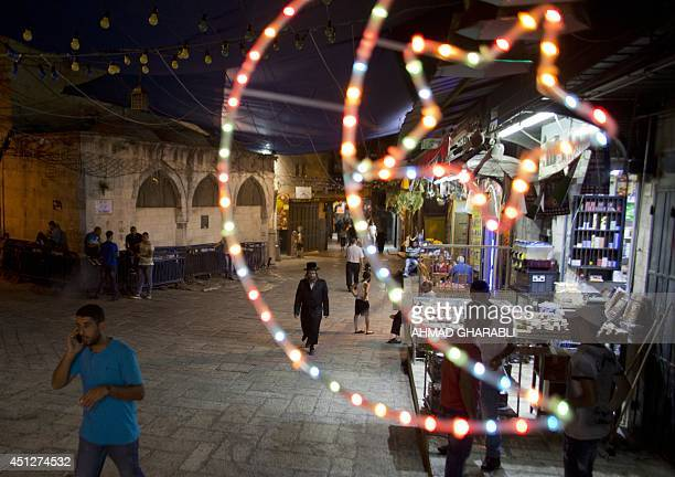 An ultra Orthodox Jewish man walks past shops decorated with lanterns near the entrance of the AlAqsa mosque compound in the old city of Jerusalem on...