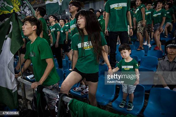 An Ultra supporter of the Beijing Guoan FC gathers with her child and others during play against Chongcing Lifan FC during their Chinese Super League...