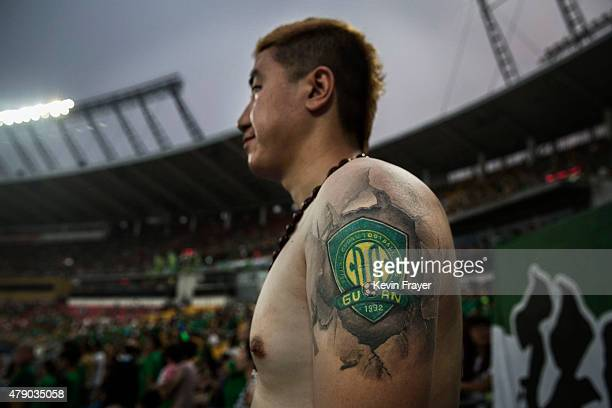An Ultra supporter of the Beijing Guoan FC shows a tattoo of the teams logo during a match against Chongcing Lifan FC in Chinese Super League play on...