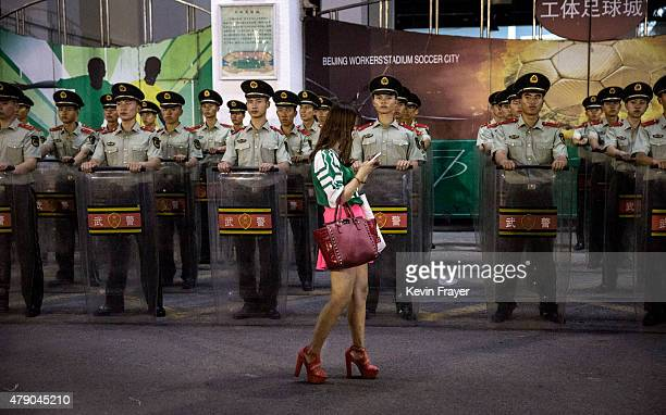 An Ultra supporter of the Beijing Guoan FC walks passed police officers following the team's Chinese Super League match against Tianjin FC on June 20...
