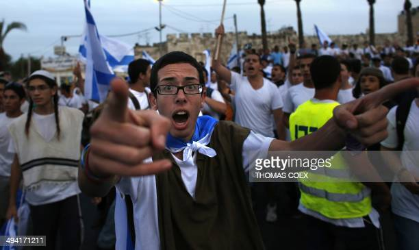 An Ultranationalist Israeli man gestures during the 'flag march' through Damascus Gate in east Jerusalem on May 28 2014 as the country celebrates the...