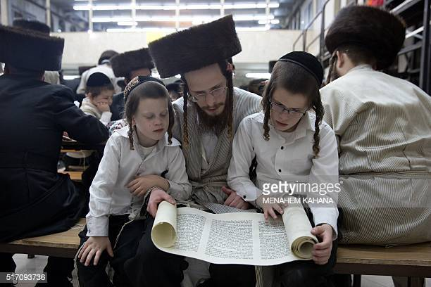 An UltraOrthodox Jew and his children read the book of Esther at a synagogue in the Israeli city of Beit Shemesh on March 23 2016 during the feast of...