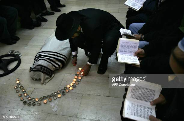 An UltraOrthodox Jew light candles as others pray before the start of the funeral of Rabbi Yitzhak Kaduri wrapped in the Talit or religious shawl 29...
