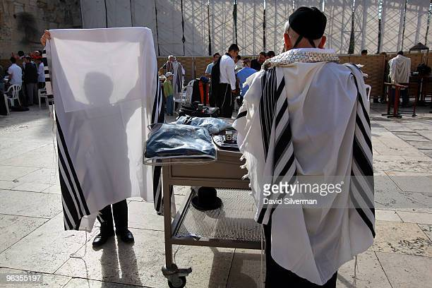 An ultraOrthodox Jew prepares to wear his Tallit or prayer shawl to join others at morning prayers at the Western Wall on February 2 2010 in...