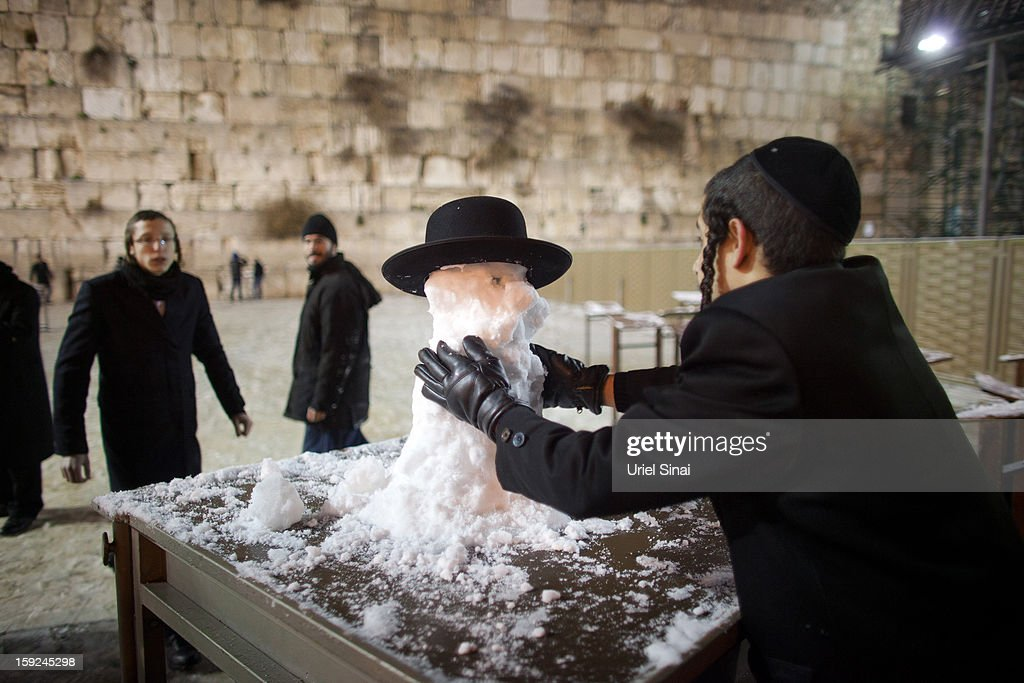 An ultra-Orthodox Jewish boy builds a snow man at the Western Wall on January 9, 2013 in Jerusalem, Israel. Snow and strong winds have affected regions across the Middle East.