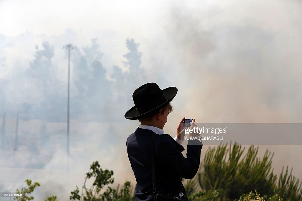 An Ultra-Orthodox Jewish boy films as firefighters work to put out a fire that is spreading in the woods around Jerusalem on May 26, 2016 / AFP / AHMAD