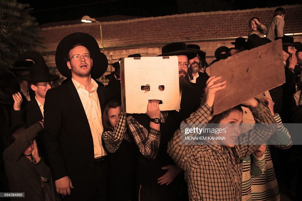 An Ultra-Orthodox Jewish boy uses a piece of cardboard to protect his face from the heat of a giant bonfire in the Mea Shearim neighborhood of Jerusalem on May 25,2016 during the celebration of Lag BaOmer. The Lag BaOmer bonfire is lit to commemorate the death of renowned Jewish scholar and renowned Bar Yochai some 1800 years ago. In a night long vigil thousands of Jews will light large bonfires and visit the final resting place of Bar Yochai, who is revered as one of Judaism's great sages. / AFP / MENAHEM
