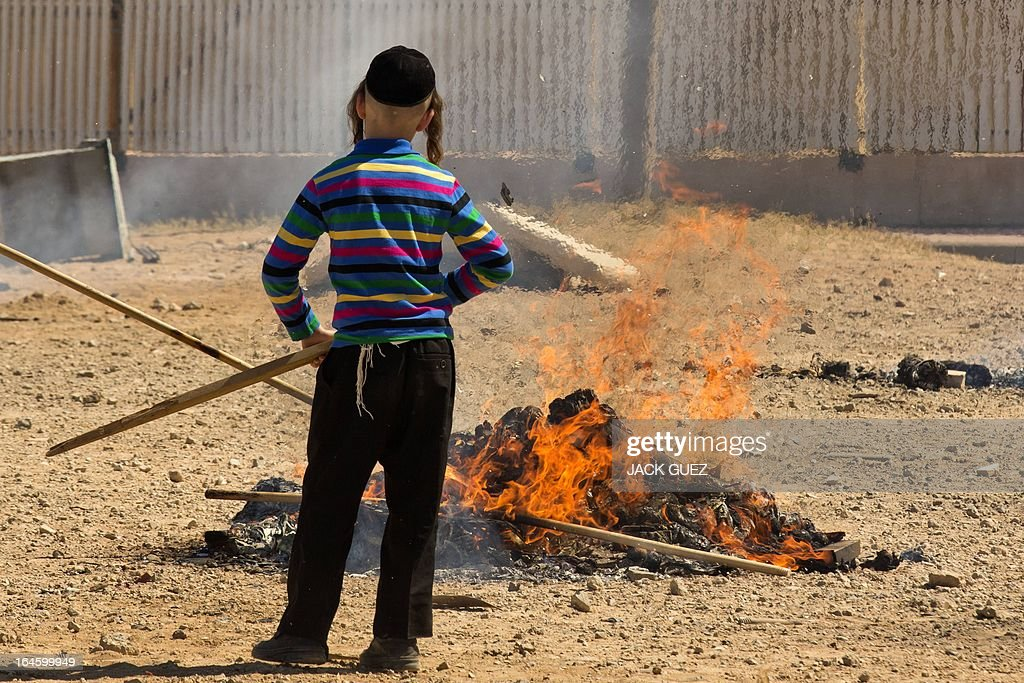 An Ultra-Orthodox Jewish boy watches leavened items burn in the final preparation before the start at sundown of the Jewish Passover holiday, in the Mediterranean coastal city of Netanya, central Israel, on March 25, 2013. All leavened food, such as bread, is forbidden to Jews during the week-long holiday, which to commemorate the Israelites' exodus from Egypt some 3,500 years ago. Due to the haste with which the Jews left Egypt, the bread they had prepared for the journey did not have time to rise. To commemorate their ancestors' plight, the religious avoid eating leavened food products throughout Passover.