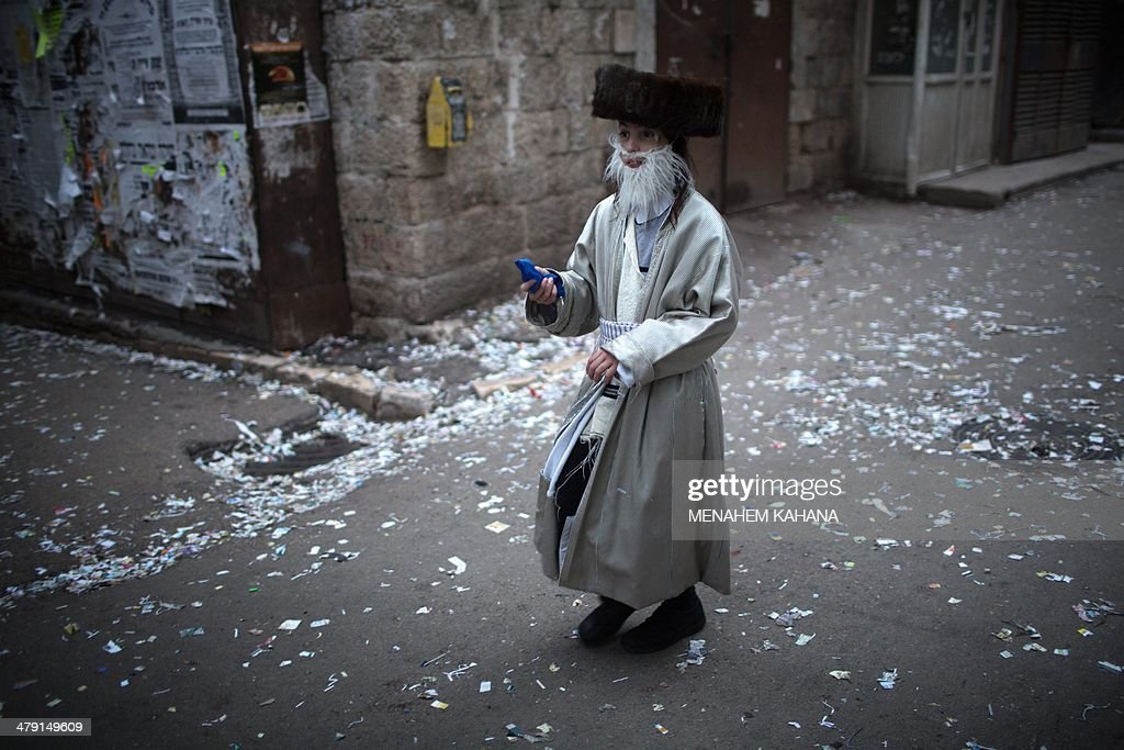 An ultraOrthodox Jewish boy wearing a costume walks in Jerusalem on March 16 2014 during the feast of Purim The carnivallike Purim holiday is...
