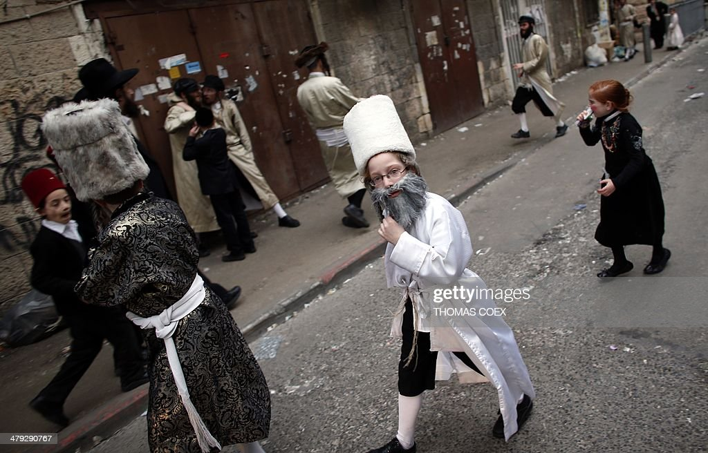 An ultraOrthodox Jewish boy wearing a costume walks in Jerusalem on March 17 2014 during the Purim holiday The carnivallike Purim holiday is...