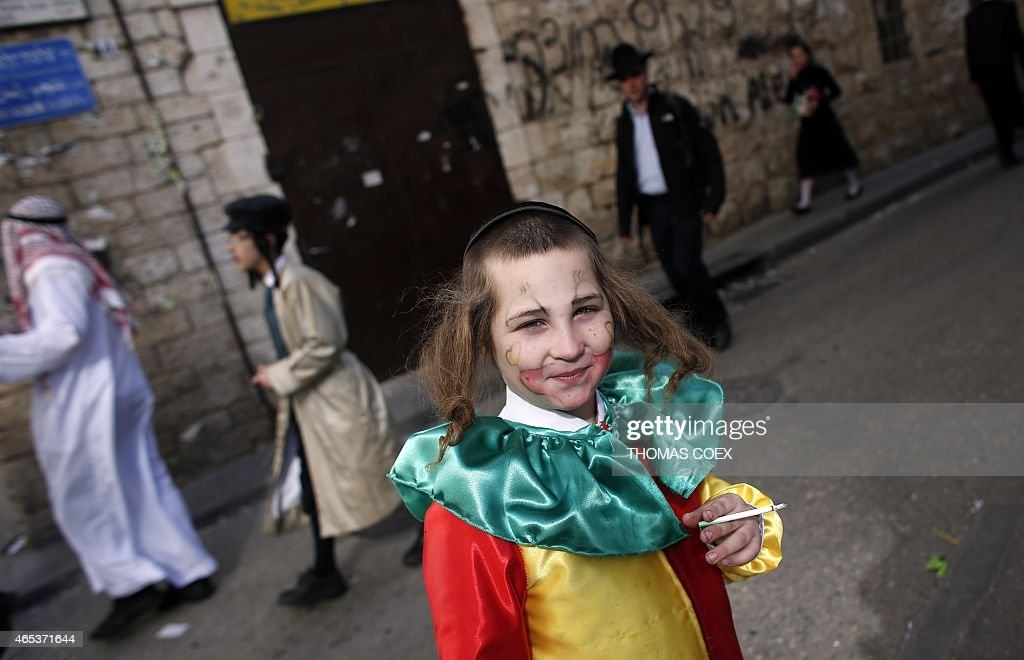 An UltraOrthodox Jewish dressed up boy smokes in a street of Jerusalem's ultraorthodox neighborhood of Mea Sharim on March 6 2015 during the feast of...
