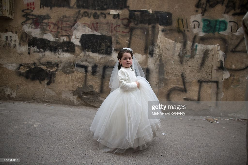 An UltraOrthodox Jewish girl dressed in costume walks in the street during the Purim holiday in the ultraorthodox Mea Shearim neighborhood in...