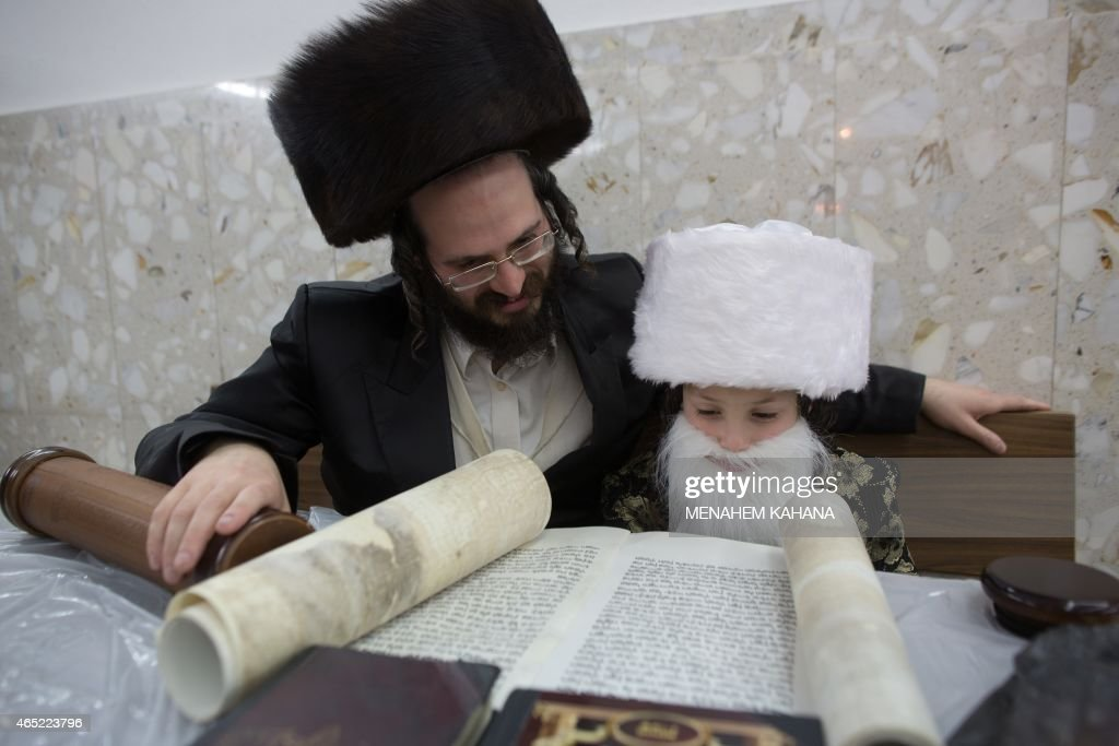 An UltraOrthodox Jewish man and his dressedup child read the book of Esther at a synagogue in the Israeli city of Bnei Brak near the costal city of...