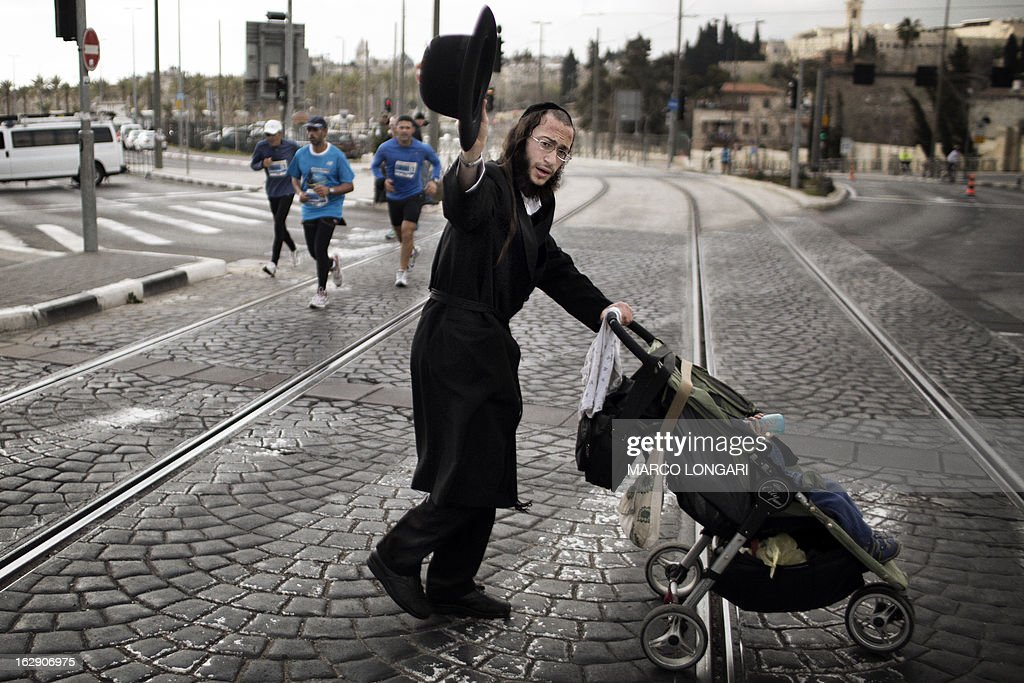 An ultra-Orthodox Jewish man gestures as he crosses a street with his child during Jerusalem's third annual marathon on March 1, 2013. About 20,000 runners took part in Jerusalem's third annual marathon, with 1,000 police deployed to provide security along the route, police said.
