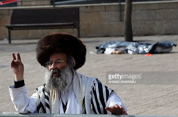 An ultraOrthodox Jewish man gestures the vsign near the body of a Palestinian assailant who was shot dead following a reported attack on December 26...