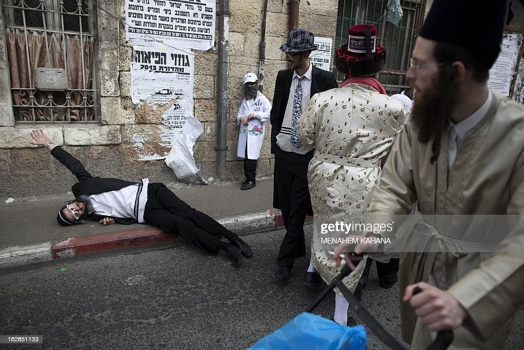 An Ultra-Orthodox Jewish man lies drunk on the sidewalk during celebrations for the Jewish festival of Purim on February 25 2013 in the religious neighborhood of Mea Shearim in Jerusalem. Purim marks the deliverance of the Jewish people from a genocidal plot in ancient Persia, as recorded in the Biblical Book of Esther.