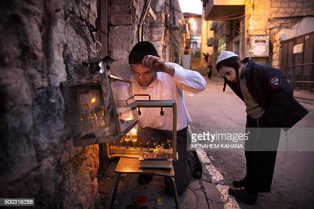 TOPSHOT An Ultraorthodox Jewish man lights candles on the second night of the Jewish holiday of Hanukkah in a religious neighborhood of Jerusalem on...