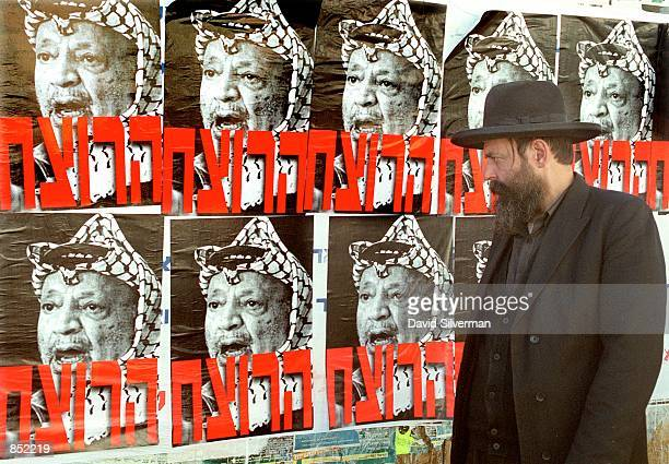 An ultraOrthodox Jewish man pauses to look at posters branding Palestinian leader Yasser Arafat as 'The Murderer' November 21 2000 in Jerusalem...
