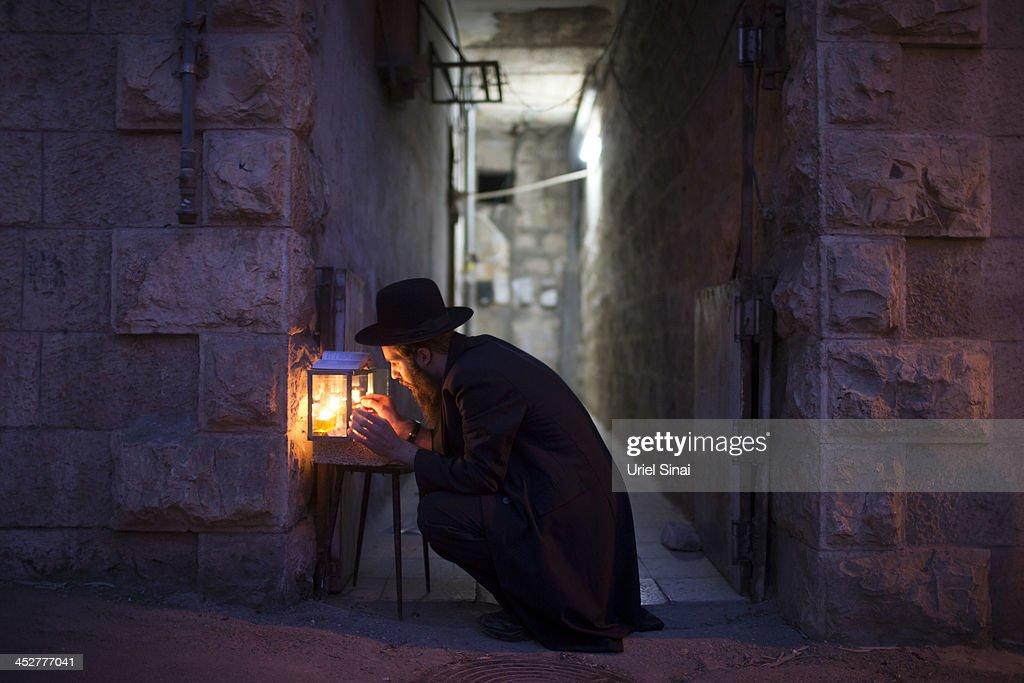 An Ultra-Orthodox Jewish man prays and lights candles on the fifth night of the Jewish holiday of Hanukkah, the festival of light, at the ultra-Orthodox neighborhood of Mea Sheaarim on December 1, 2013. in Jerusalem, Israel. Hanukkah commemorates the re-dedication of the Jewish Temple in Jerusalem in 165 BC following the victory of the Jewish Maccabees over the Seleucid Empire when there was only enough consecrated olive oil to fuel the eternal flame in the Temple for one day but miraculously, the oil burned for eight days.