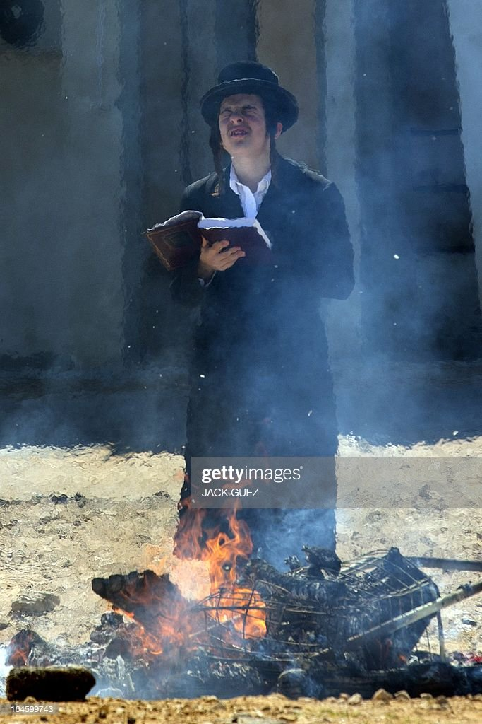 An Ultra-Orthodox Jewish man prays as leavened items are burnt in the final preparation before the start at sundown of the Jewish Passover holiday, in the Mediterranean coastal city of Netanya, central Israel, on March 25, 2013. All leavened food, such as bread, is forbidden to Jews during the week-long holiday, which to commemorate the Israelites' exodus from Egypt some 3,500 years ago. Due to the haste with which the Jews left Egypt, the bread they had prepared for the journey did not have time to rise. To commemorate their ancestors' plight, the religious avoid eating leavened food products throughout Passover.