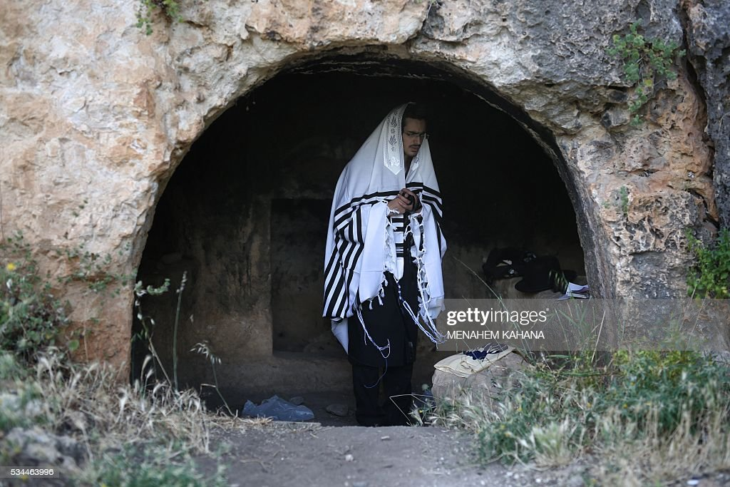 An Ultra-Orthodox Jewish man prays near the grave site of Rabbi Shimon Bar Yochai in the northern Israeli village of Meron, on May 26 2016, at the start of the day-long holiday of Lag Baomer that commemorates the Jewish scholar's death. Thousands of religious Jews light large bonfires all night long and visit the shrine of Bar Yochai, one of the most prominent sages in Jewish history, during the holiday. KAHANA