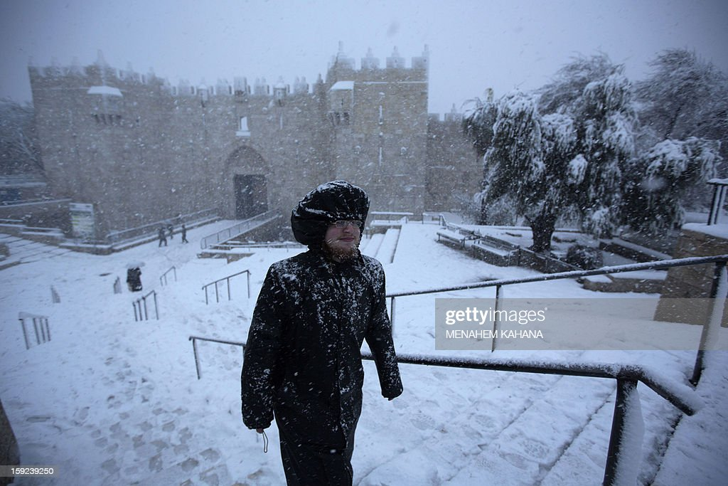 An ultra-orthodox Jewish man runs as snow falls next to Damascus gate in the old city of Jerusalem on January 10, 2013. Jerusalem was transformed into a winter wonderland after heavy overnight snowfall turned the Holy City and much of the region white, bringing hordes of excited children onto the streets. AFP PHOTO/MENAHEM KAHANA