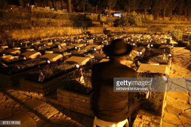 An ultraOrthodox Jewish man sits next to the grave of a loved one on April 30 at the Mount Herzel military cemetery in Jerusalem at the start of...